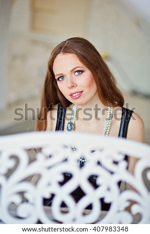 Beautiful woman with long brown hair in black dress playing the piano - stock photo
