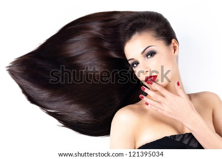 Beautiful woman with long brown straight hairs and elegance red nails - stock photo