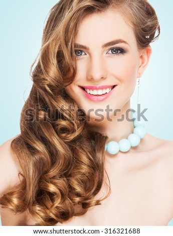 Beautiful woman with long curly brown hair. Glamour smiling female. Studio shot - stock photo