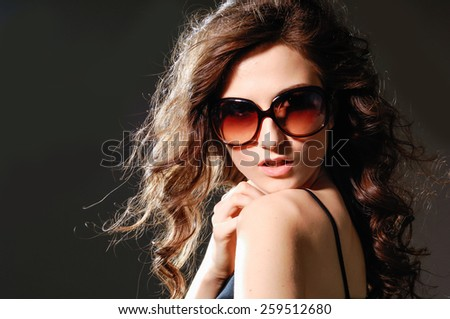 Beautiful woman with long curly hair with sunglasses - stock photo