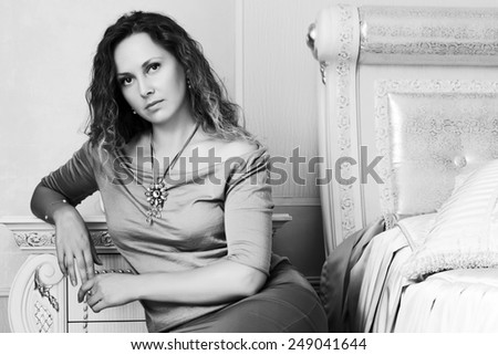 Beautiful woman with long curly hairs in a bedroom - stock photo