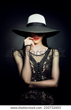 Beautiful woman with long dark hair and red lips in fashioned hat. Black background.