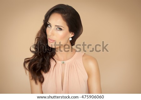 Beautiful woman with long dark hair on beige background.