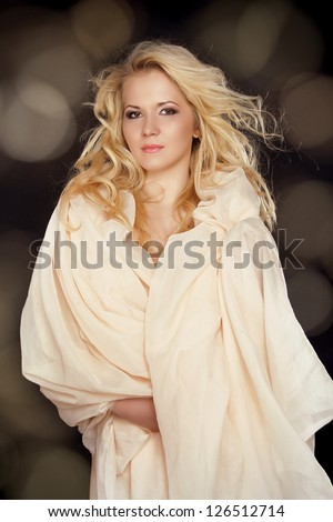 Beautiful woman with long  fair hair and fabric scarf over black - stock photo
