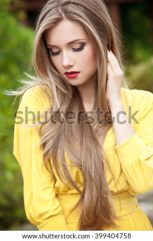 Beautiful woman with long hair. Fashion girl in summer park - stock photo