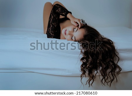 beautiful woman with long hair in bed at home - stock photo