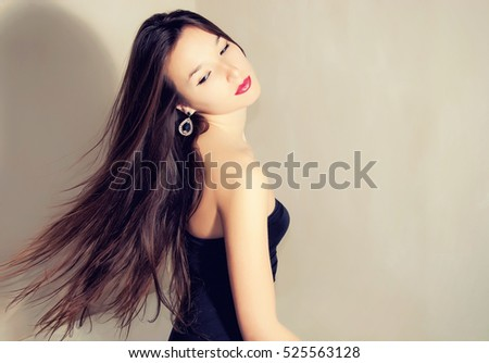 Beautiful woman with long hair in black dress.