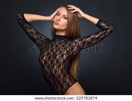 Beautiful woman with long hair in black lace lingerie, semi-dress posing in studio. - stock photo