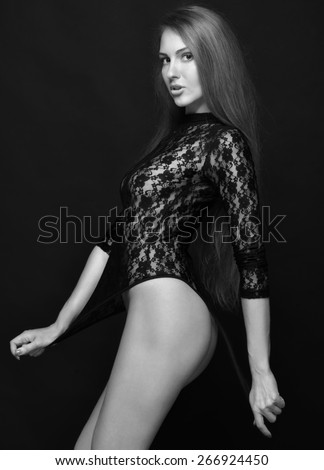 Beautiful woman with long hair in black lace lingerie, semi-dress posing in studio. Monochrome image.
