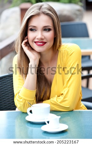 Beautiful woman with long hair in the street cafe drinking coffee