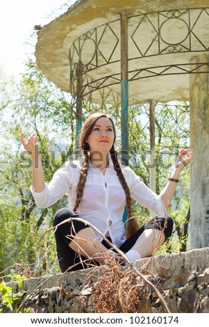 Beautiful woman with long hair meditating near architecture with columns, nature of Almaty at background  / Young woman doing yoga
