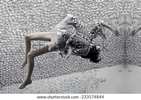 beautiful woman with long legs in design dress jump up - stock photo