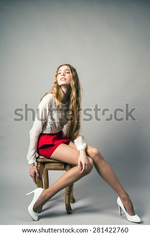 beautiful woman with long legs in red dress posing in the studio - stock photo
