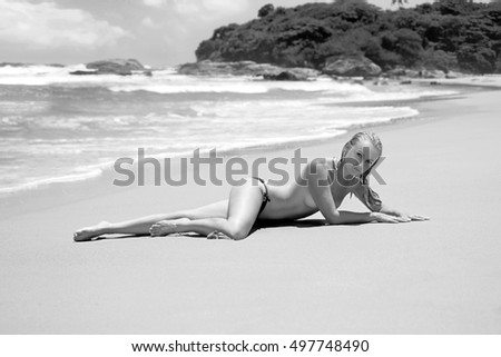 Beautiful woman with long legs in the blue bikini on the lonely beach in the rays of the sun. Black and white photo.
