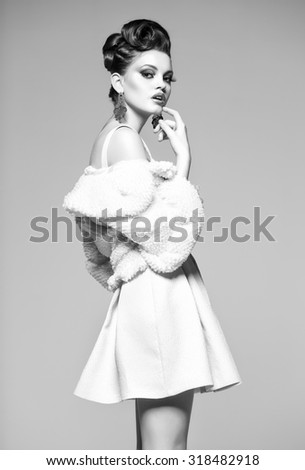 beautiful woman with long legs in white dress, fur and high-heels posing in the studio - stock photo