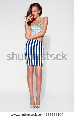 beautiful woman with long sexy legs dressed sexy posing in the studio - full body, holding soda - stock photo