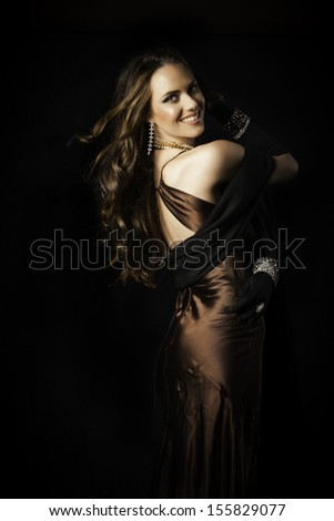 Beautiful woman with long, shiny brown hair hanging in soft curls down her exposed back, dressed in bronze satin evening dress.