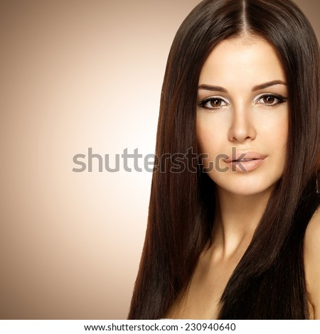 Beautiful woman with long straight brown hair. Fashion model posing at studio over beige background
