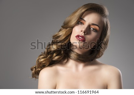 beautiful woman with long wavy hair and dark dress, she looks in to the lens with head folded at left - stock photo