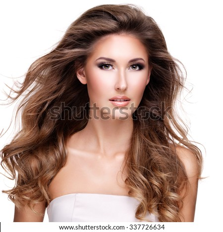 Beautiful woman with long wavy hair posing at studio. Isolated on white background