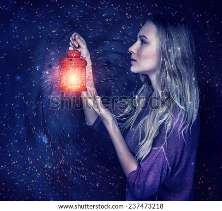 Beautiful woman with magic lantern on starry sky background, holding in hands red vintage lamp, antique festive attributes, Christmas holidays - stock photo