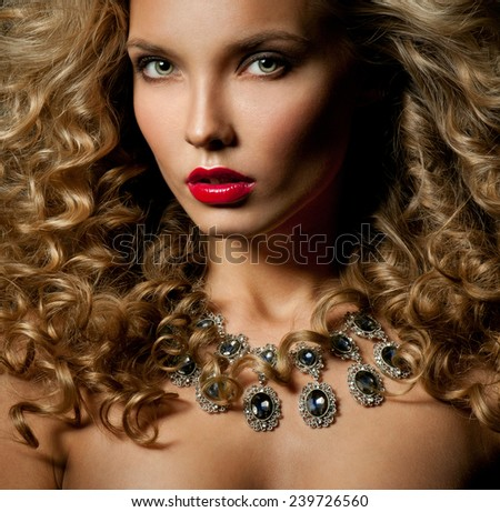 Beautiful woman with magnificent curly hair. Red lipstick. Necklace.