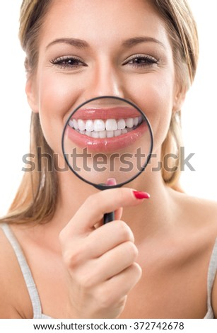 Beautiful woman with magnifying glass showing her perfect white teeth - stock photo