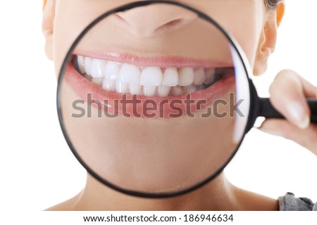 Beautiful woman with magnifying glass showing her perfect white teeth. Over white background. - stock photo