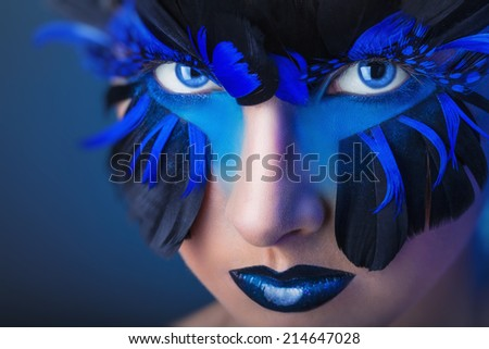 Beautiful woman with make-up with blue feathers - stock photo