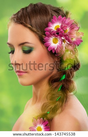 Beautiful woman with makeup and flowers over green background