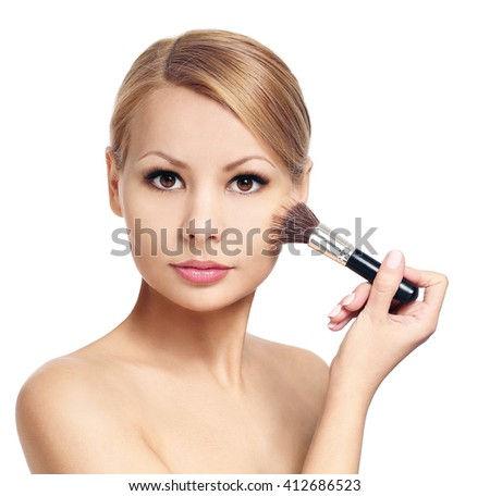 Beautiful woman with makeup brush isolated on white. Blonde girl applying blush on her cheek