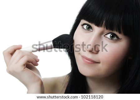 Beautiful woman with makeup brush near her face - stock photo
