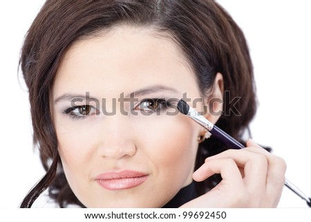 Beautiful woman with makeup brush near her face - isolated on white