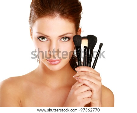 Beautiful woman with makeup brushes near her face - stock photo
