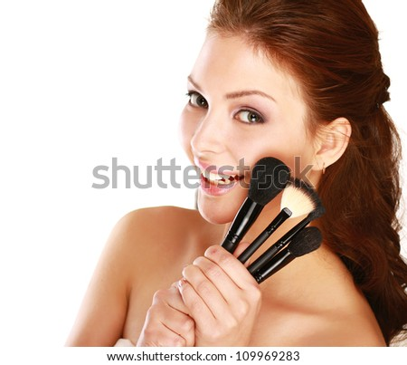 Beautiful woman with makeup brushes near her face isolated on white background