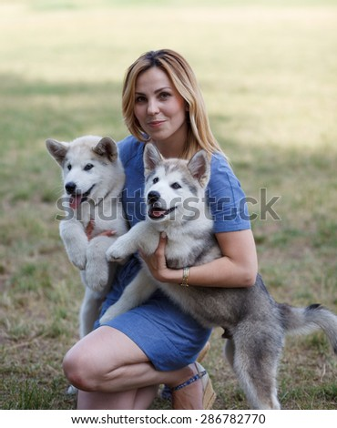 Beautiful woman with malamutes puppies;Outdoor portrait