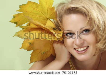 beautiful woman with maple leaves over light green background