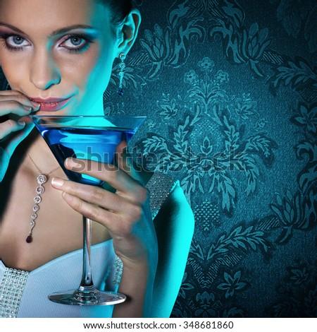 Beautiful woman with martini glass on damask wallpaper background. - stock photo