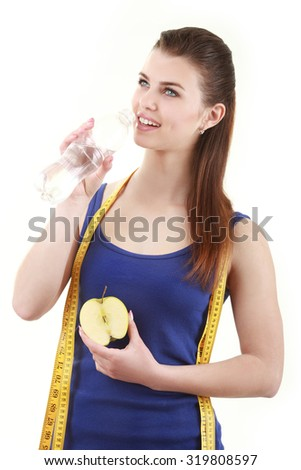 Beautiful woman with meter tape holding bottle of water and apple on white background