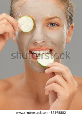 beautiful woman with mud mask cucumber slices - stock photo