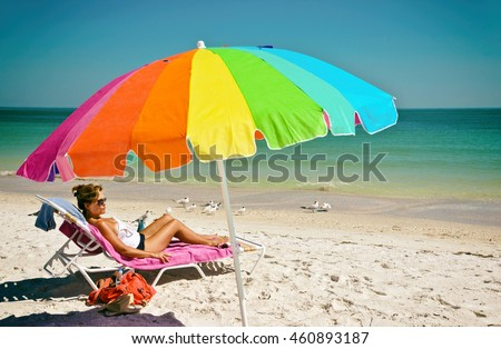 Beautiful Woman with Multi-Color Umbrella Enjoying a Day at the Beach on Anna Maria Island, Florida