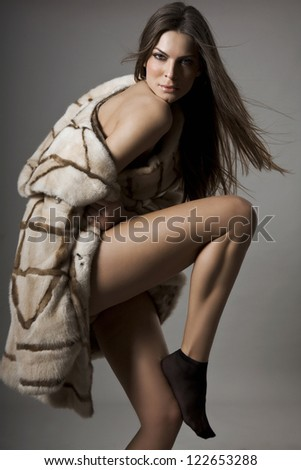 Beautiful woman with naked shoulder in fur coat