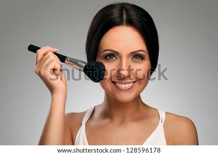 Beautiful woman with natural makeup and brush isolated over background