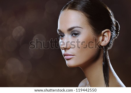 beautiful woman with natural makeup in long earrings and boke lights on the broun background - stock photo
