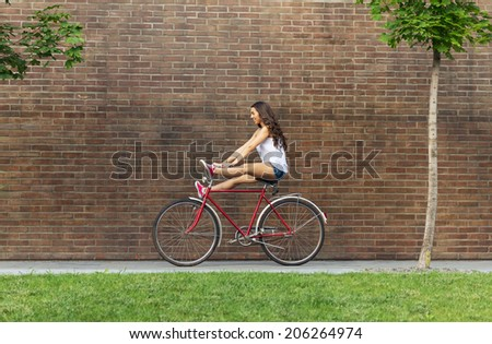 Beautiful woman with old bike in front of a brick wall  - stock photo