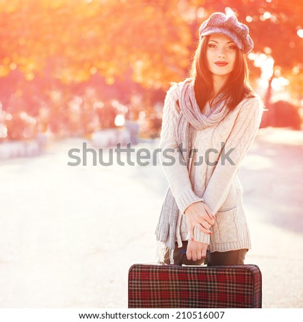 Beautiful woman with old suitcase on the street