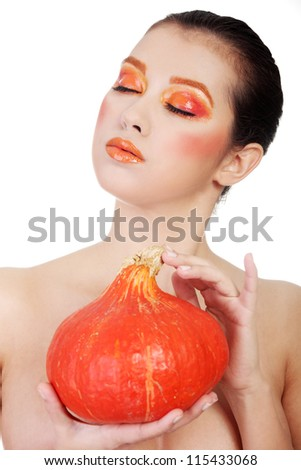 Beautiful woman with orange make up holding pumpkin - stock photo