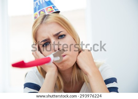 Beautiful woman with party hat and blows whistle - stock photo