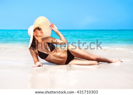 Beautiful Woman With Perfect Body Lying Down On The Beach, Wearing Stylish  Hat, Tanning