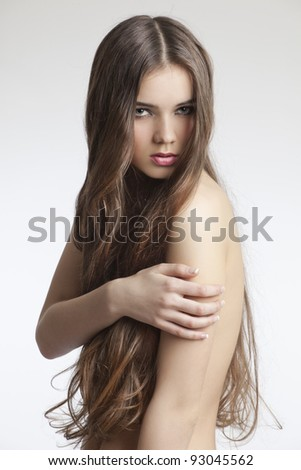 beautiful woman with perfect skin and long curly hair on a white background - stock photo